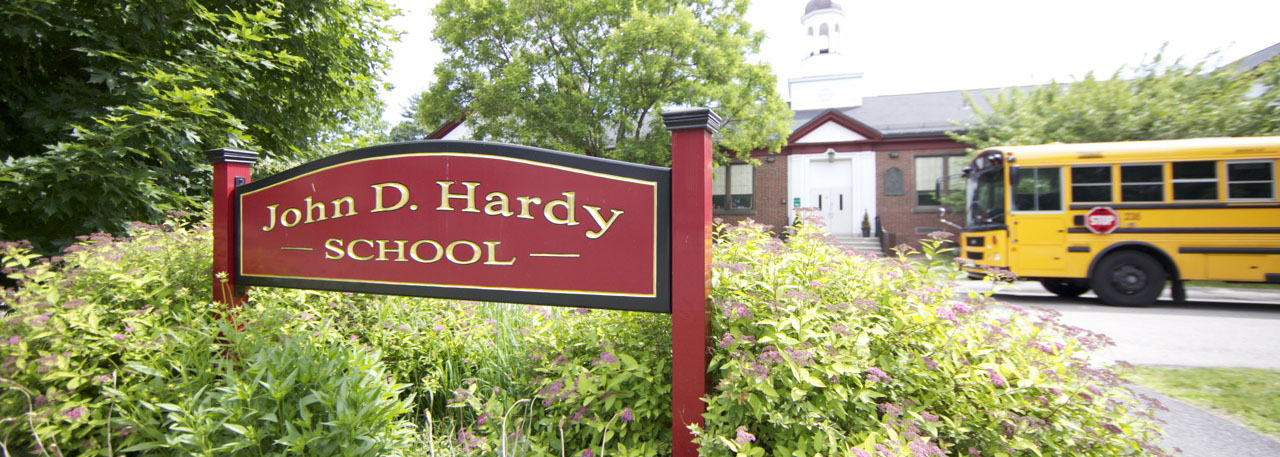 Hardy School exterior with sign and school bus