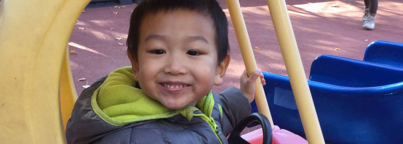 PAWS student on the playground in a ride-on car