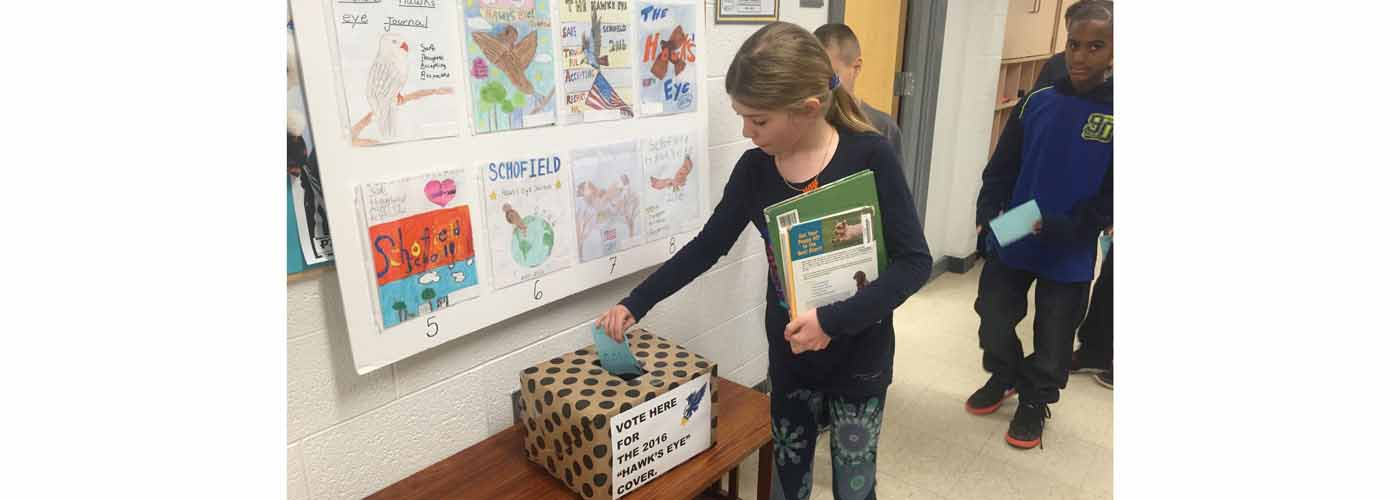 Schofield student casting a ballot to vote on the Hawk\'s Eye cover