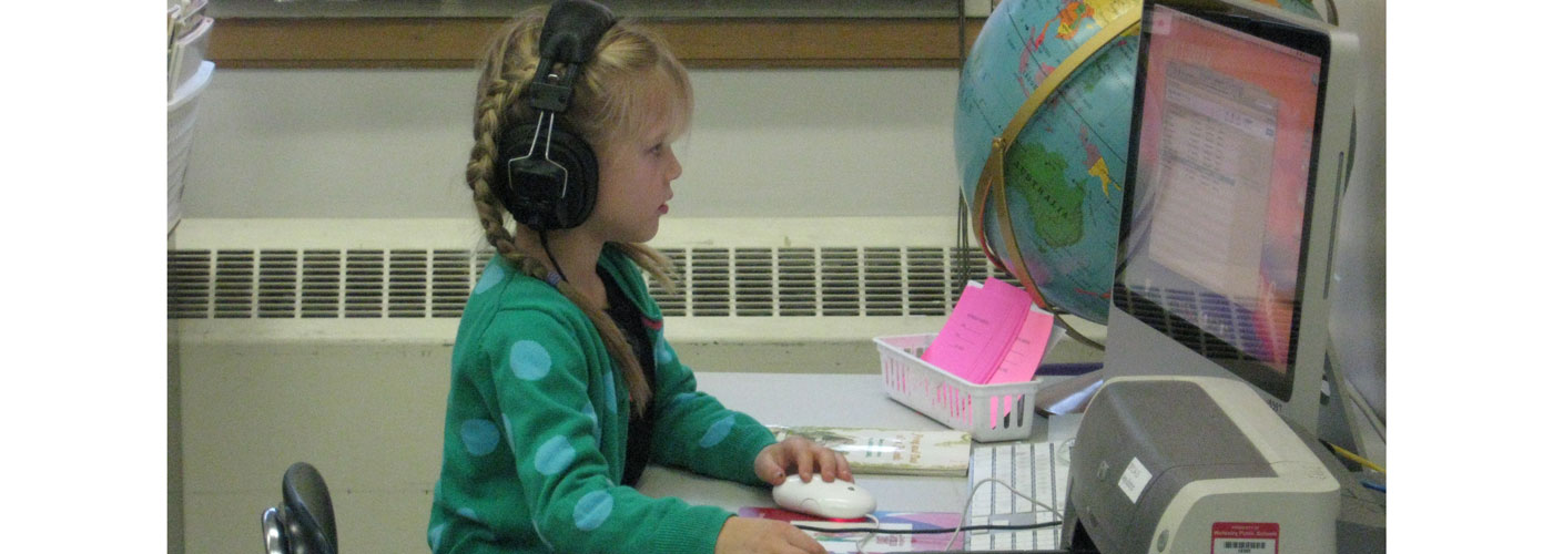 Upham student using a computer with headphones