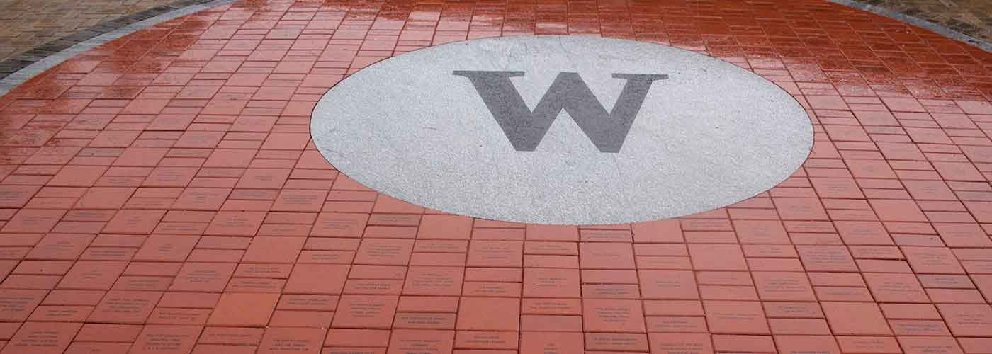 The letter W for Wellesley on the pavement in front of school surrounded by red bricks on a rainy day