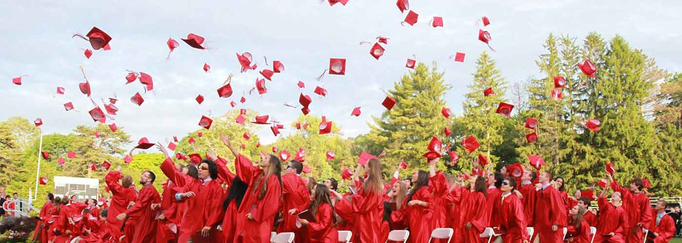 WHS students in red gowns throwing their caps in the air during graduation