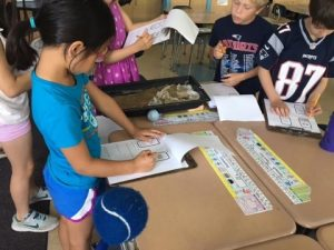 Second grade students test different solutions to solving the problem of erosion.