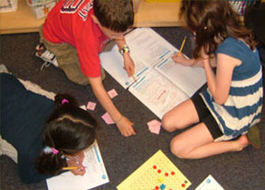 group of students working on math on the floor